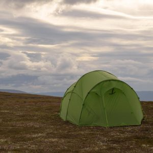 Quadratic tent pitched on a plateau with clouds behind