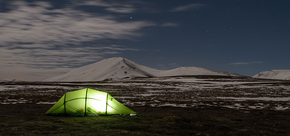 Quadratic tent lit from inside at night with snow hills and stars
