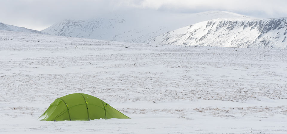 Quadratic Tent with snow ridges behind