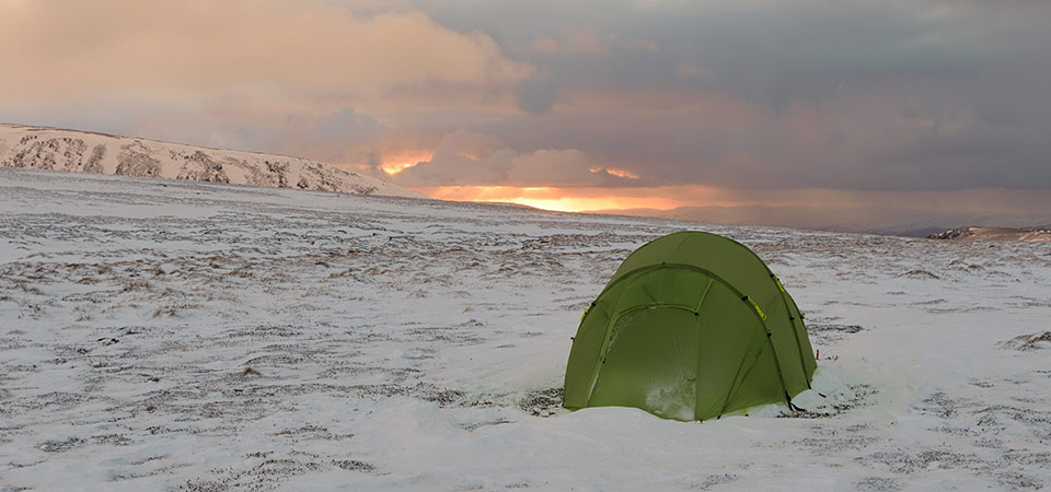 Quadratic tent on snow with sunset behind