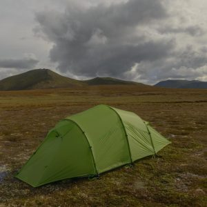 Quadratic tent pitched on a plateau with dark clouds