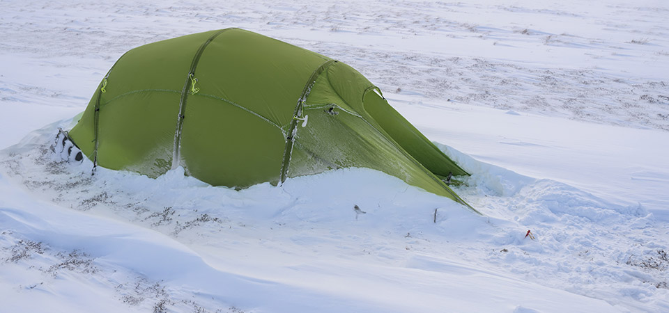 Quadratic tent pitched in windblown snow.