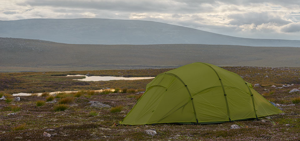 Quadratic tent pitched on a plateau with tarns and hills behind