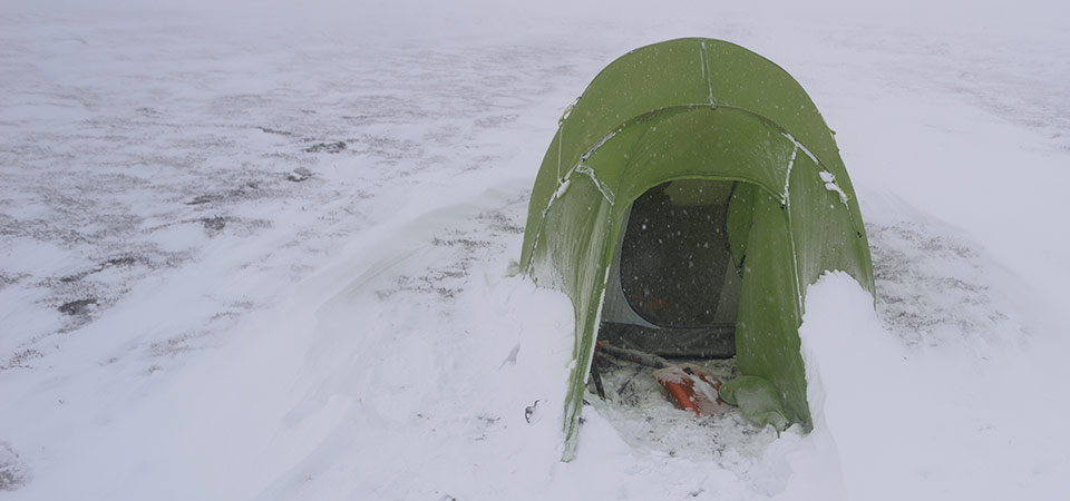 Quadratic tent door with windblown snow