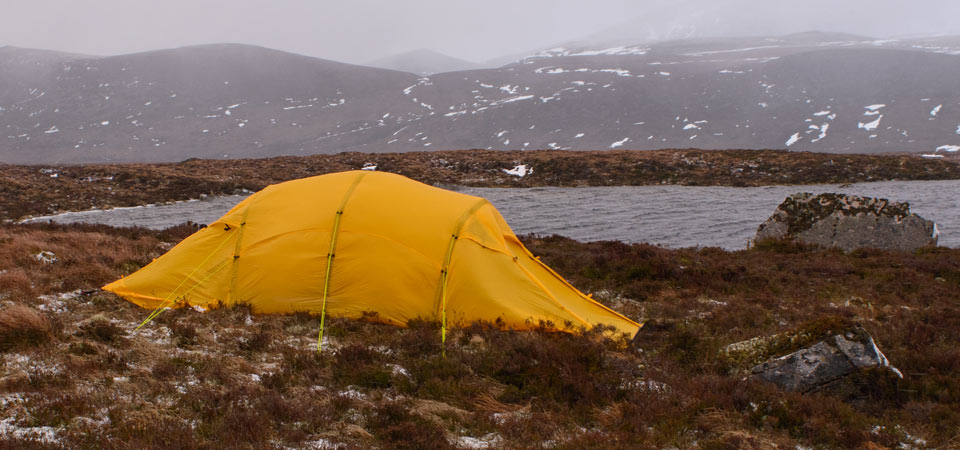 Quadratic tent pitched by a lake in high winds